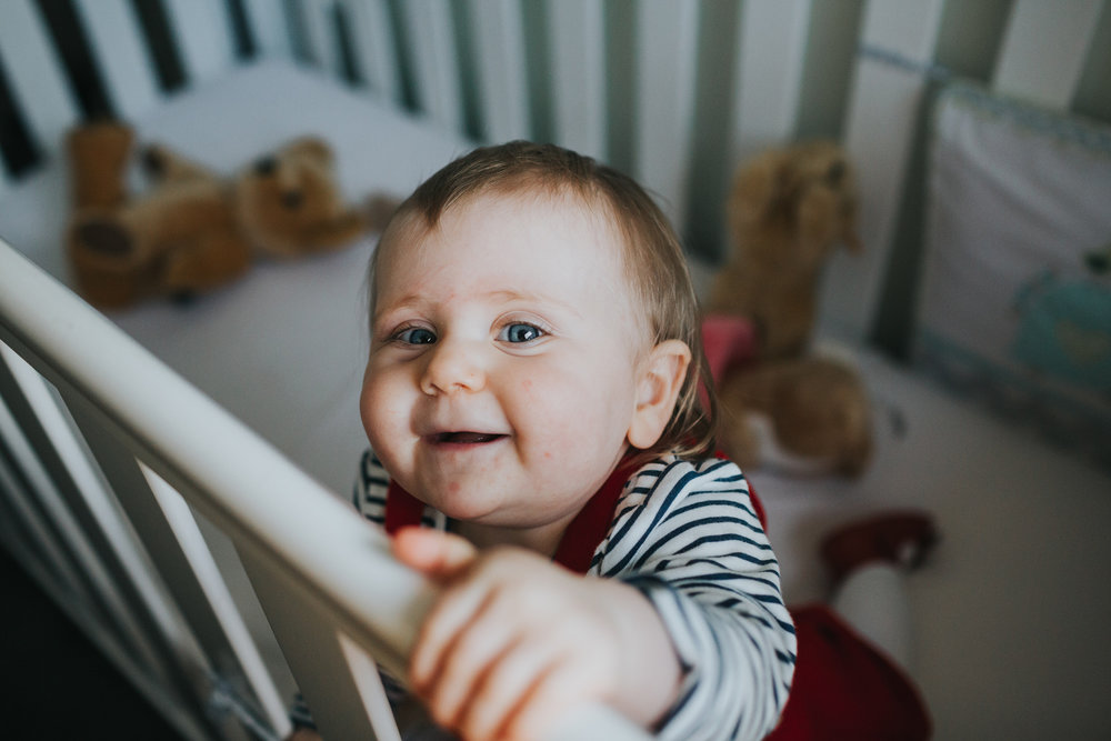 One year old child pulls herself up on the  cot with a cheeky smile.