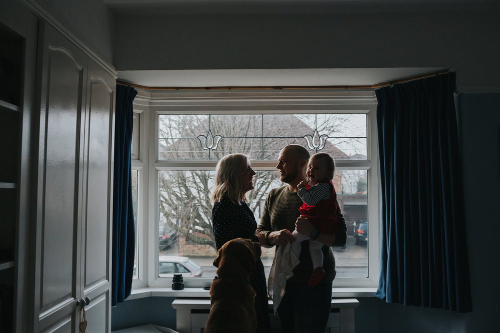 Silhouette of family standing together in front of the master bedroom window.