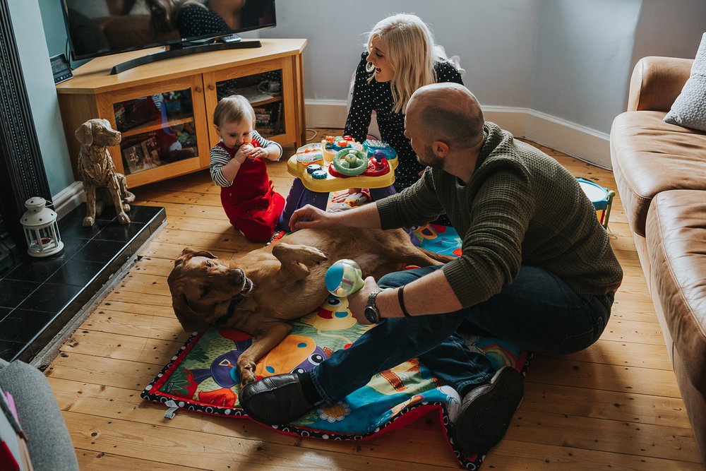 Family play together on the living room floor.