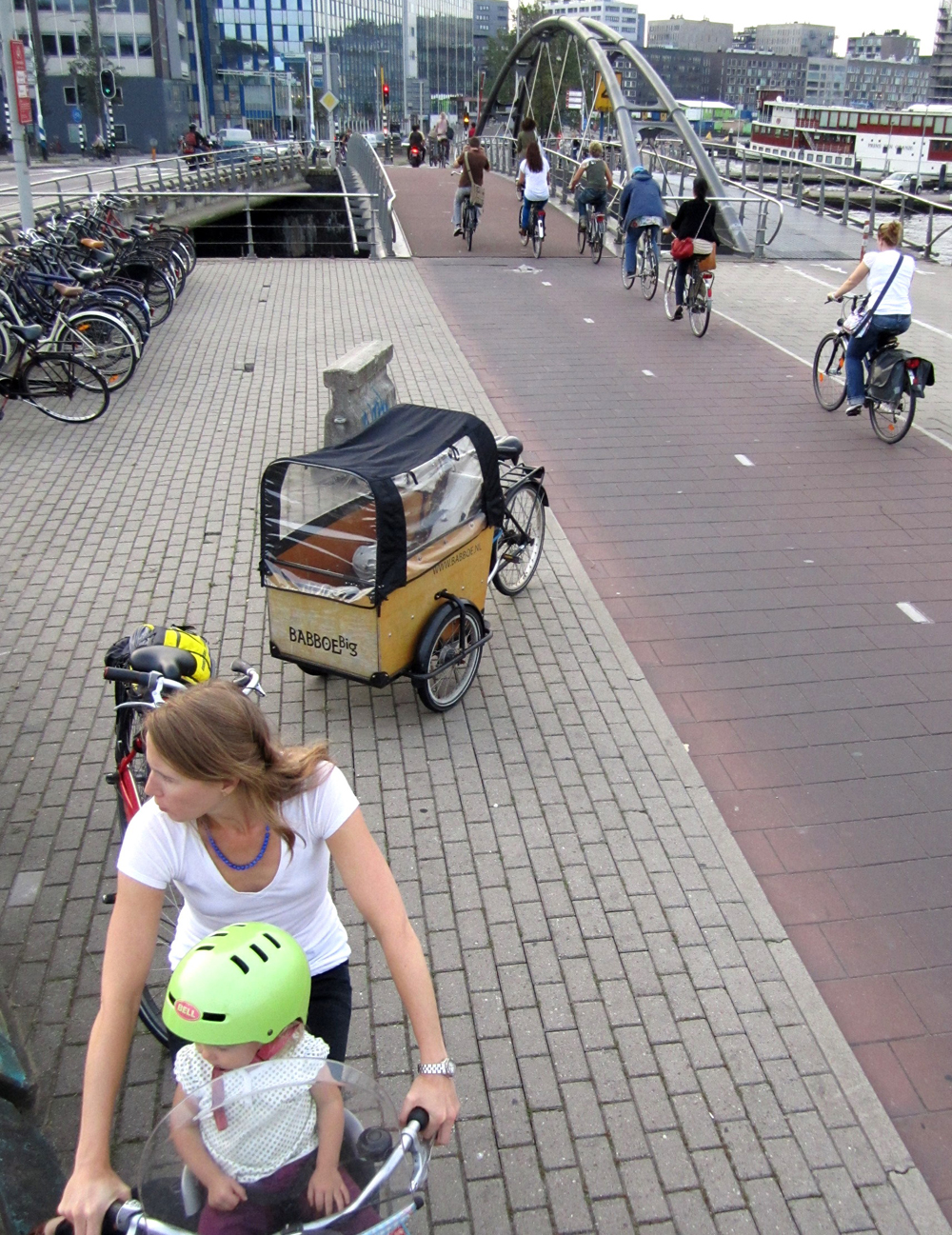 Founder, Megan Ramey, biking in Amsterdam on family vacation with her 2 year old daughter. The vision for North America of normal living by bike is why she has pledged to donate 25% of Bikabout's annual revenue every year.