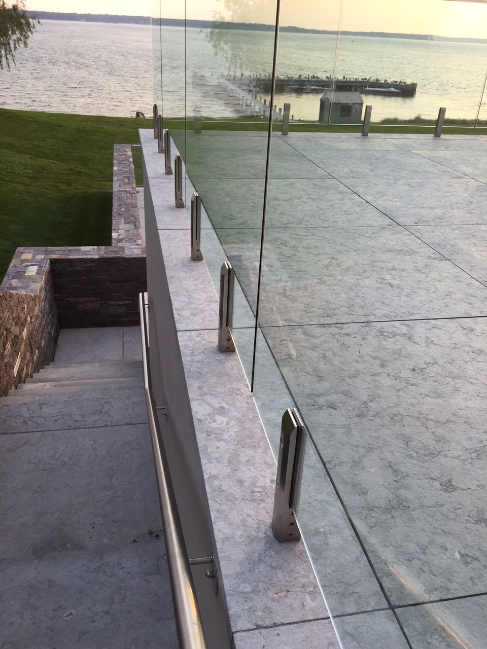 One of the major successes of this project is making the railing as unobtrusive as possible. Glass panels that are held in place by stainless steel clamps from the base are secured to the pavers, set in concrete.