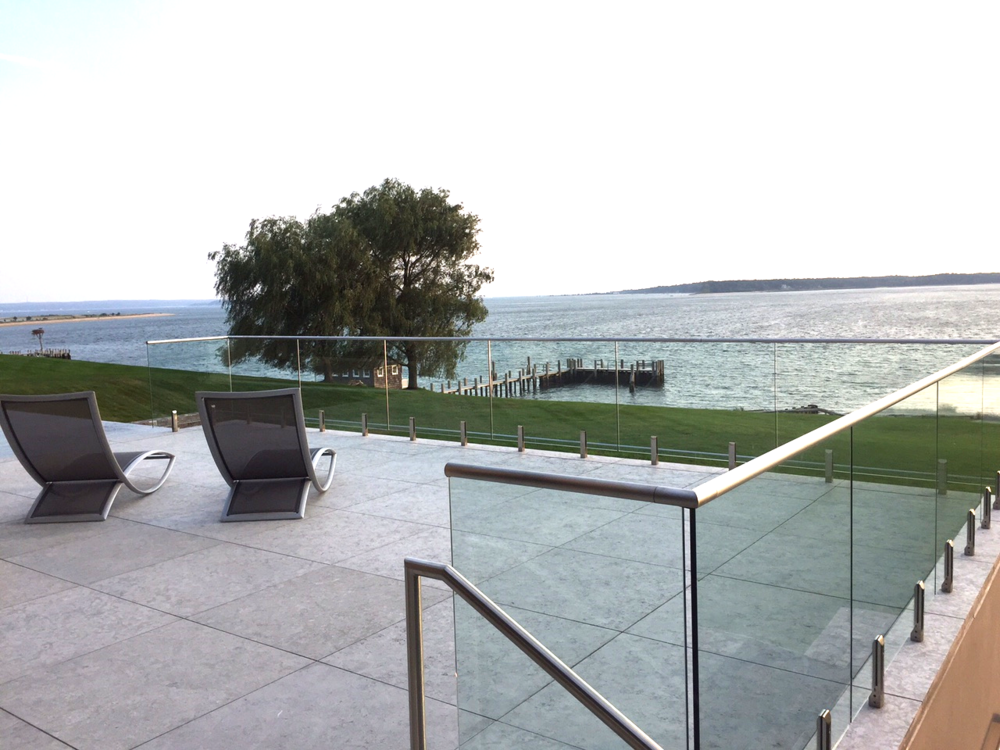 The view out towards the bay is unobstructed with a wrapping glass rail that recedes from your view. The paving is a limestone paver shipped from Portugal, 2' x 2' in a square grid pattern.  The scale is just right for the size of the terraces, and love the light grey color with the light texture so not so slippery when wet. An alternative to purchasing limestone pavers from Portugal is a company based in CA:  View Product Website