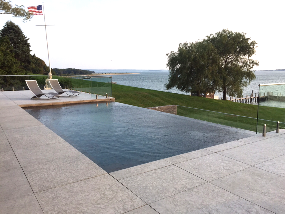 The limestone pavers are cut to extend right to the edge of this dark-bottom infinity edged pool. Pools were installed by a company called Binder Pools, located on Shelter Island.