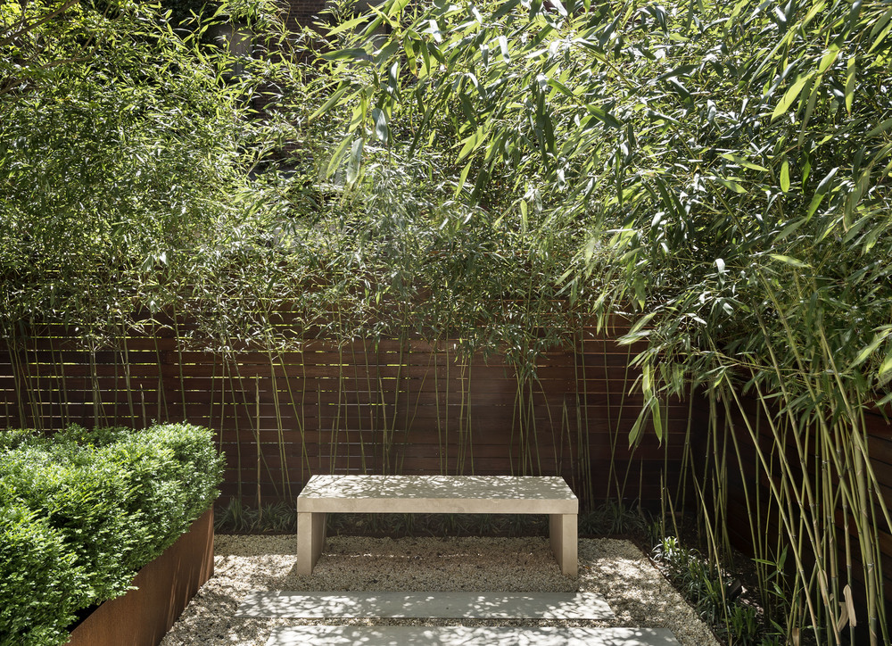 A  focal point: it helps to think about what you want to notice in a garden, and hierarchy. This simple stone bench provides a quiet place to sit and also a design element that draws your eye out into the landscape from the house. View Product Website