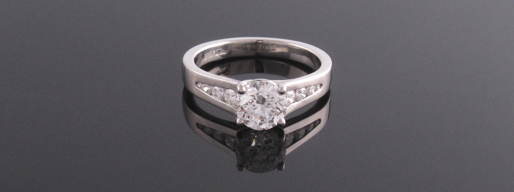 Platinum 4 claw diamond solitaire engagement ring with channel set shoulders