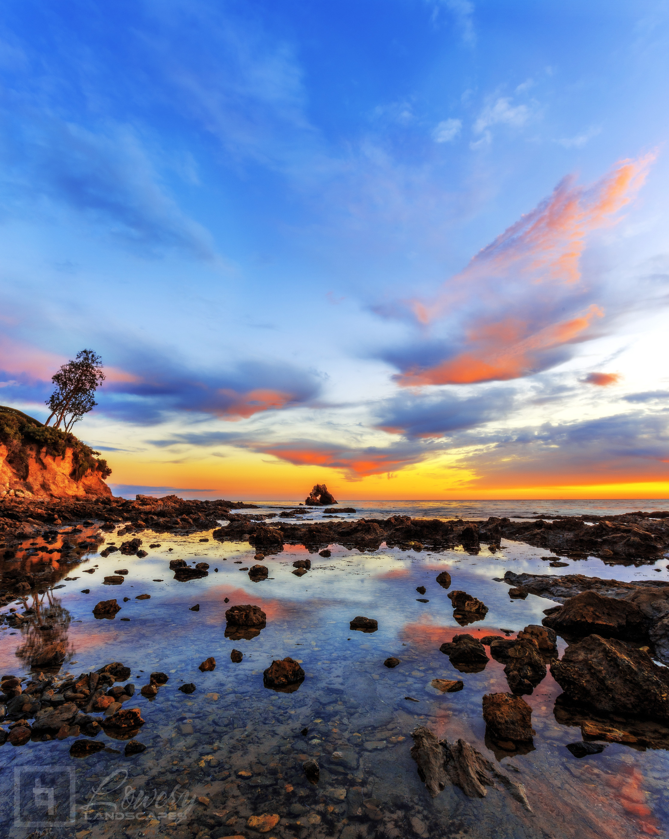 The colors clouds lit by the setting sun are reflected in these tranquil tidal pools along the Southern California coast.