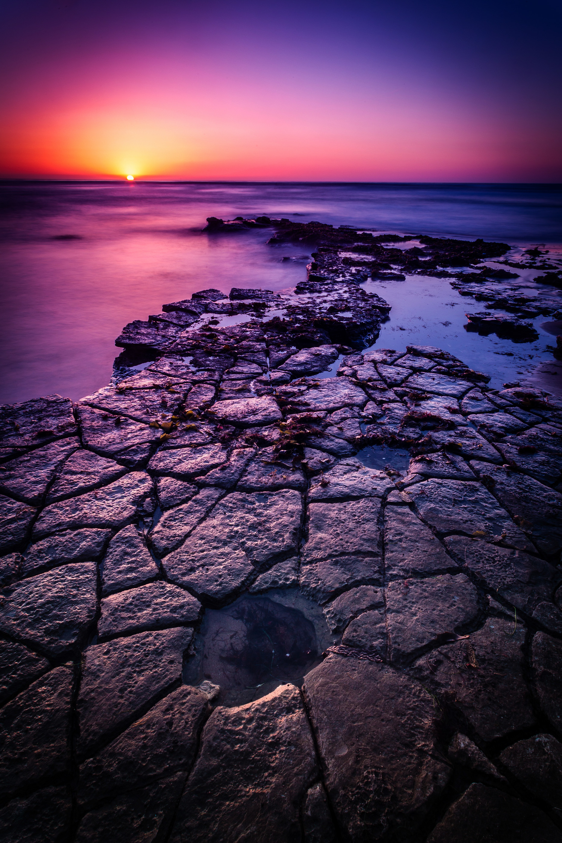 The orange sun begins to dip below the pacific horizon as it casts its last glow on the puzzle at Sunset Cliffs in Point Loma, near San Diego California.