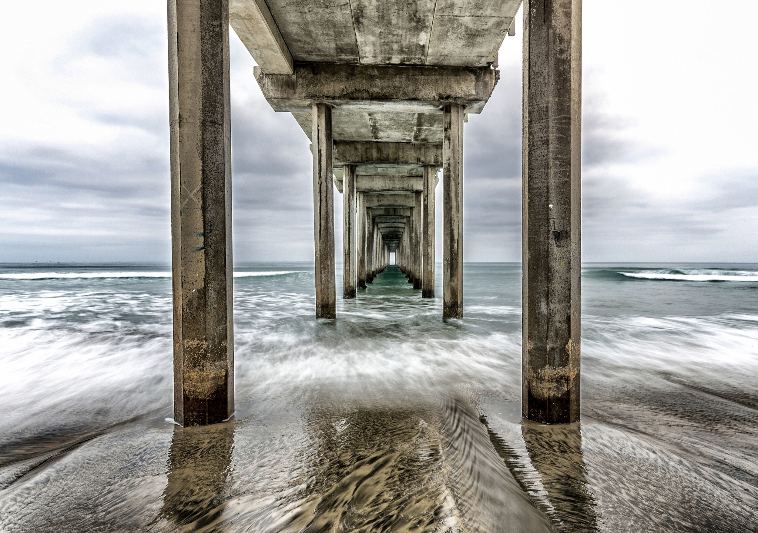 Waves are captured in mid-cycle at dawn beneath this oceanography research pier in La Jolla, California.