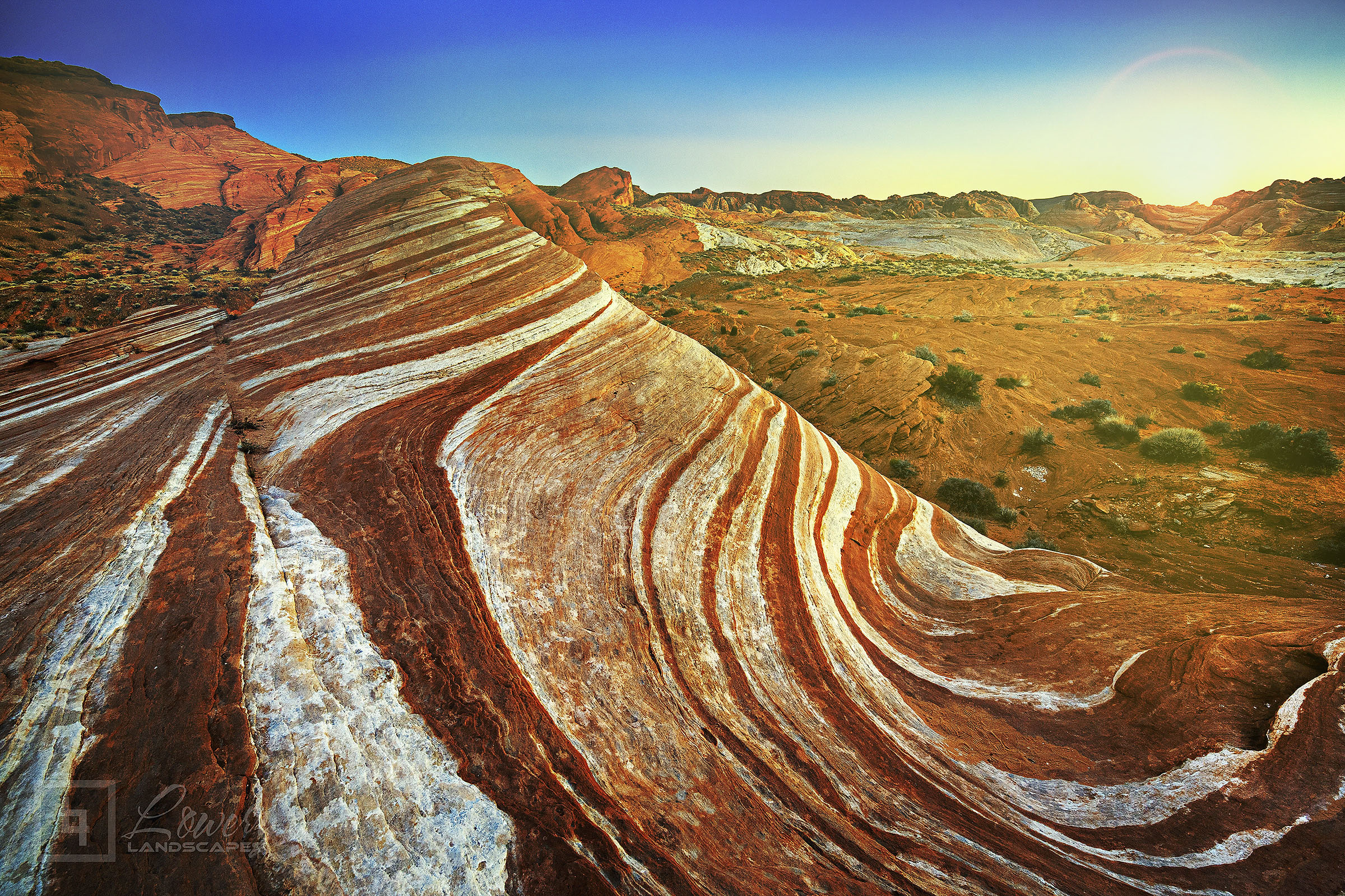 Massive waves of vividly designed sandstone in the Nevada desert simmer in the heat of the setting summer sun.