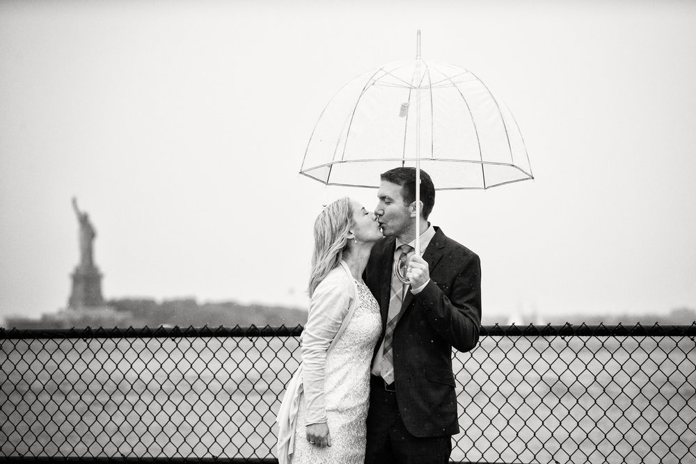 Following their wedding on Governor's Island, a couple has their portrait taken by the Statue of Liberty on a rainy day.