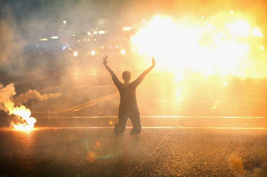 Above image of protester in Ferguson, MO taken by Getty Images photographer Scott Olson, who was arrested on Monday, August 18 2014 by law enforcement officials