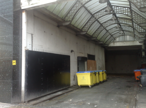 The roof of Lewis's Arcade visible above the bin store