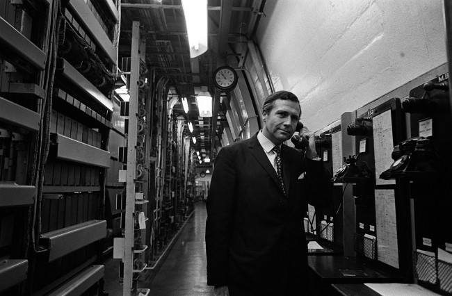 """(Image and caption from  Flashbak ) From 150 ft below Manchester's city centre, Mr John Stonehouse, the Postmaster General, makes a call from the deep level telephone exchange. The exchange was designed """"to protect against total interruption of the telephone trunk service in severe emergency"""". * Mr Stonehouse took the opportunity to visit the deep-level exchange while in Manchester to open the new Rutherford trunk exchange which is situated above ground. Date: 07/10/1968"""
