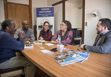 PBN PHOTO/ MICHAEL SALERNO PERSEVERANCE: Urban Ventures Executive Director Jr Neville Songwe, second from left, meets with staff and microbusiness owners. The public incubator, which continues to operate, is at risk of closing due to loss of funds.