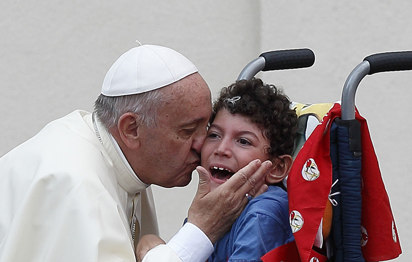 Pope Francis kisses a child as he arrives to greet participants in the Renewal of the Spirit meeting in St. Peter's Square at the Vatican July 3. (CNS photo/Paul Haring)