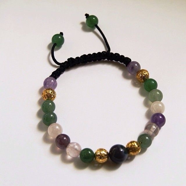 New to the shop! An exquisitely designed & carefully handcrafted men's bracelet featuring jade, amethyst and white shell semi precious stone beads accented with gold plated filigree beads and hand woven fully adjustable black nylon cording.