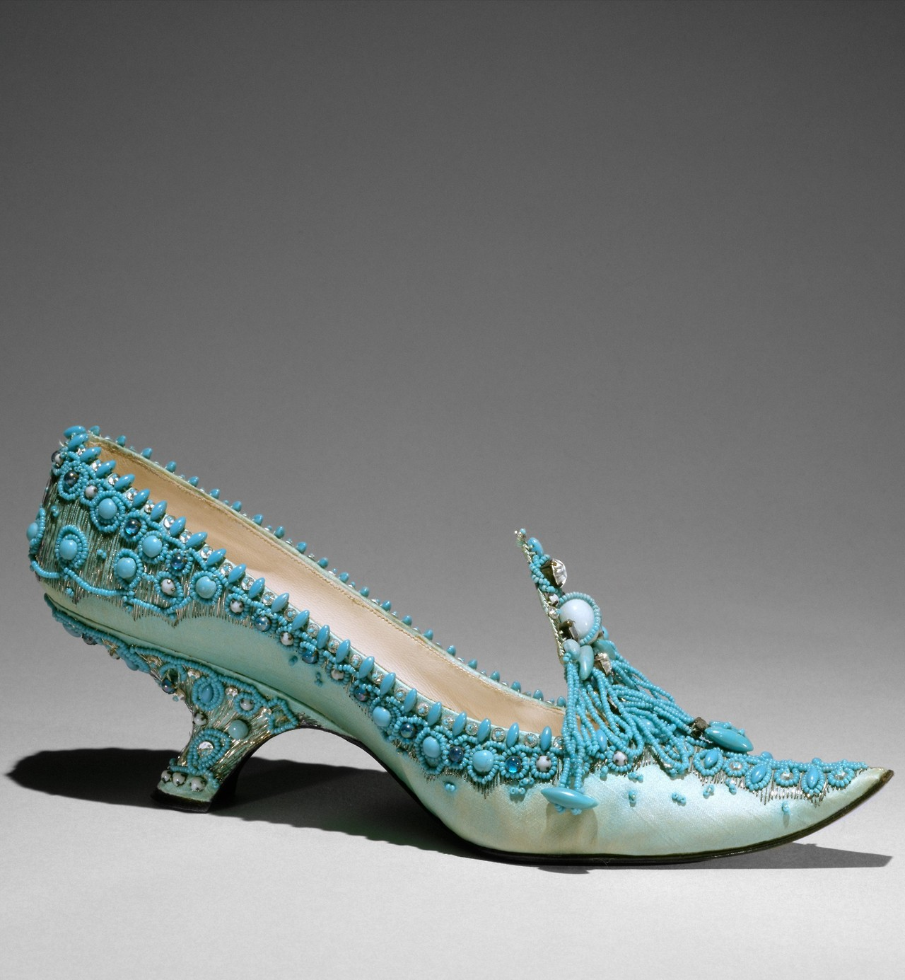 fashioninhistory :       Evening Pump       Roger Vivier for Christian Dior       1961      Roger Vivier, the shoe designer for Christian Dior from the 1940s to the '60s, was known for his exquisite forms and extravagant materials. In this evening pump, he took the upturned toe and turquoise blue associated with the glazes and semiprecious stones of the Middle East to create his version of the Orientalist slipper. While the sleek contours of Vivier's shoes invariably narrowed the natural shape of the foot, his innovative heel treatments add tension and even a feeling of incredulity to his designs.