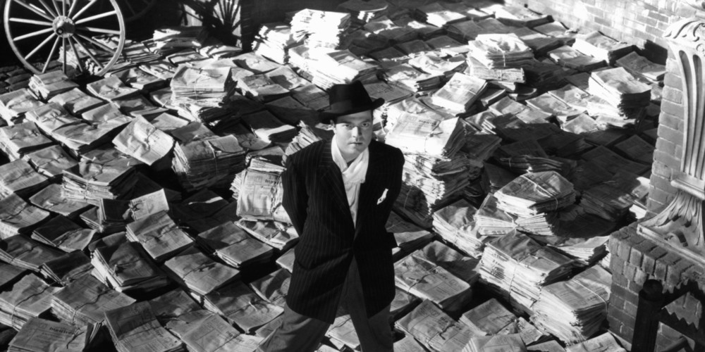 Orson Welles, pictured with a more literal wall of newspapers
