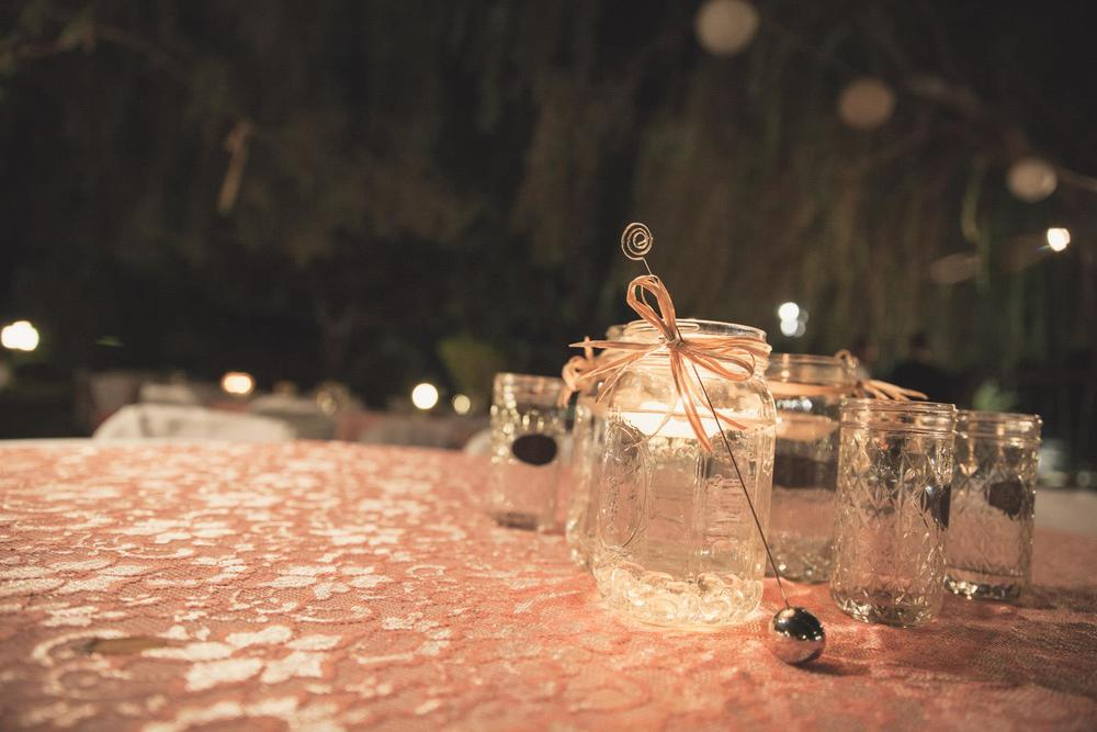 Mason Jars with candles floating in water on each table at their outdoor reception