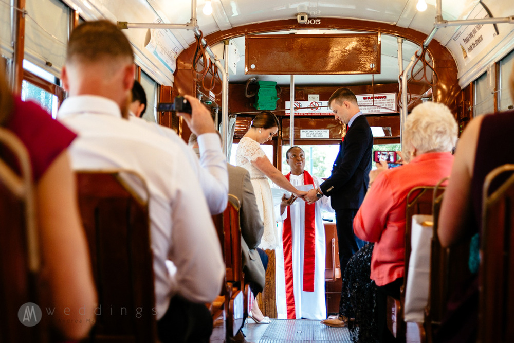 The officiant says a prayer during the wedding ceremony aboard the New Orleans streetcar. Having a streetcar wedding was perfect for an intimate ceremony, and made for a unique collection of photographs.