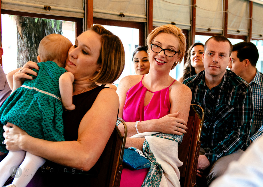 A guest smiles during Corbie and Brian's wedding ceremony aboard the New Orleans streetcar. Having a streetcar wedding was perfect for an intimate ceremony, and made for a unique collection of photographs.