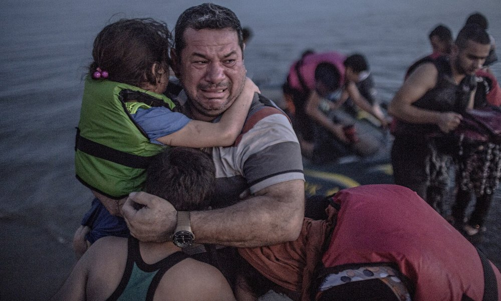 Main photograph by Daniet Etter/New York Times/Redux /eyevine. Laith Majid cries tears of joy and relief that he and his children have made it to Europe.