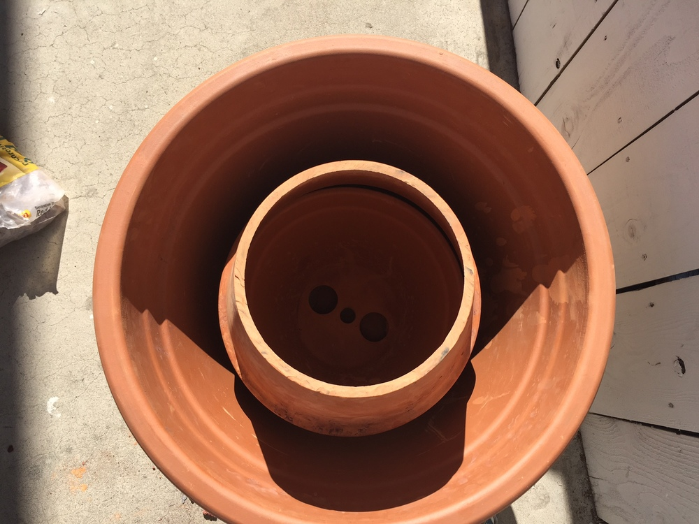 Invert the middle sized pot over the smallest one inside the largest, outer pot. This will create an interior cylinder.