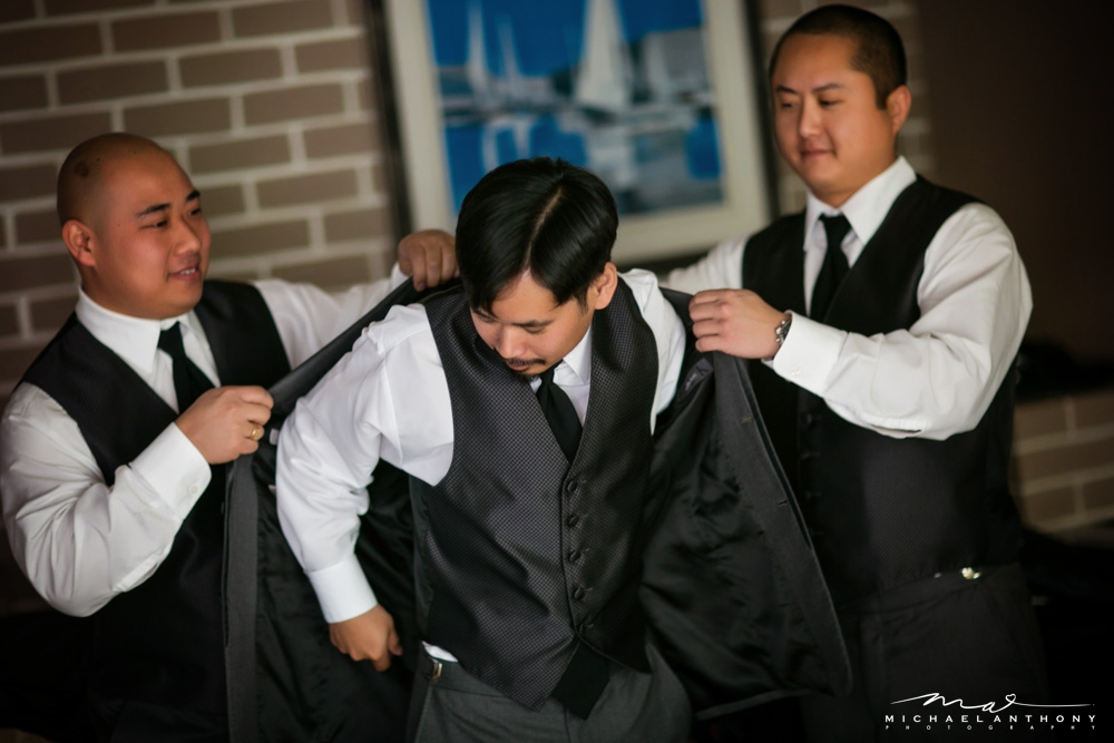 The groom putting on his jacket