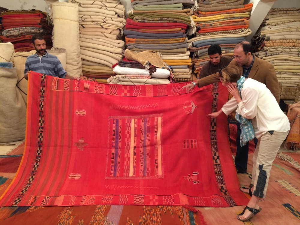 Hakim explains an antique silk carpet