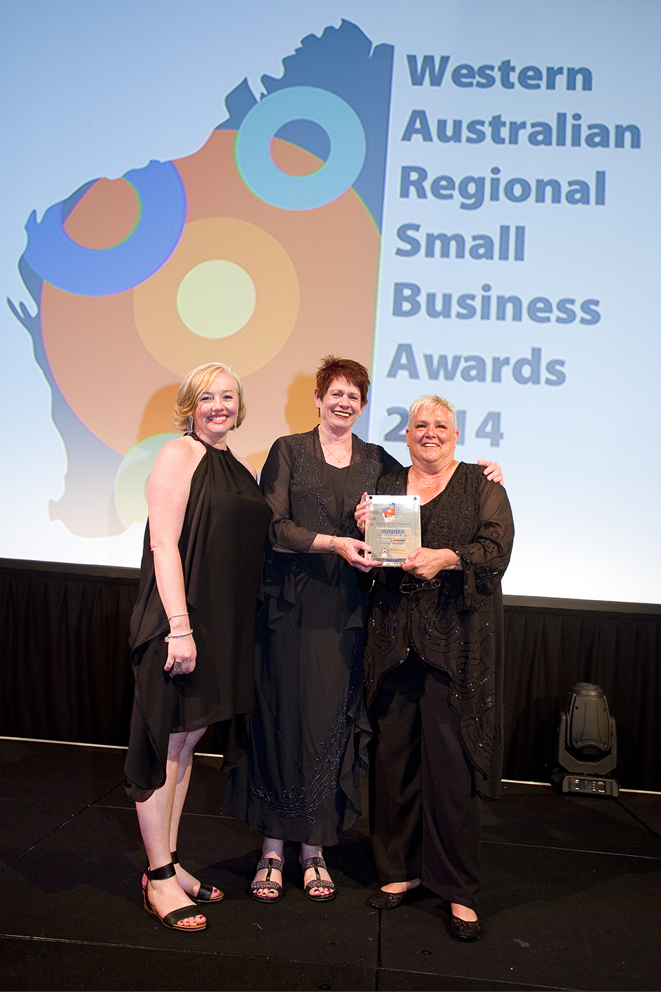 Top photo: Bronte Holmes, of Qantas, presents Maggie van Santen and Becki Shaver, of HideAway Haven, with their prestigious gong at the 2014 WA Regional Small Business of the Year Awards. Picture: Murray Armenti.