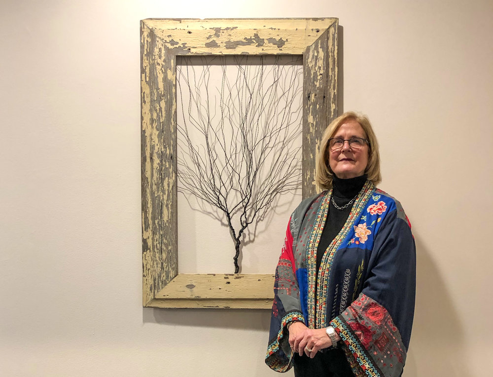 Gail Neuman stands beside one of about 25 steel wire trees she has sculpted the past two years. Her poplar-like recreation is displayed at The Omni, a Long Island corporate building with a lobby that doubles as an art gallery. (Photo: Joseph Kellard)
