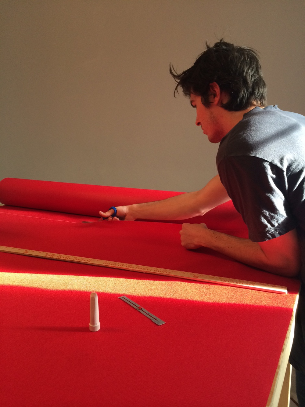 Kelsey prepping a large sheet of cordura for the cutting machine.
