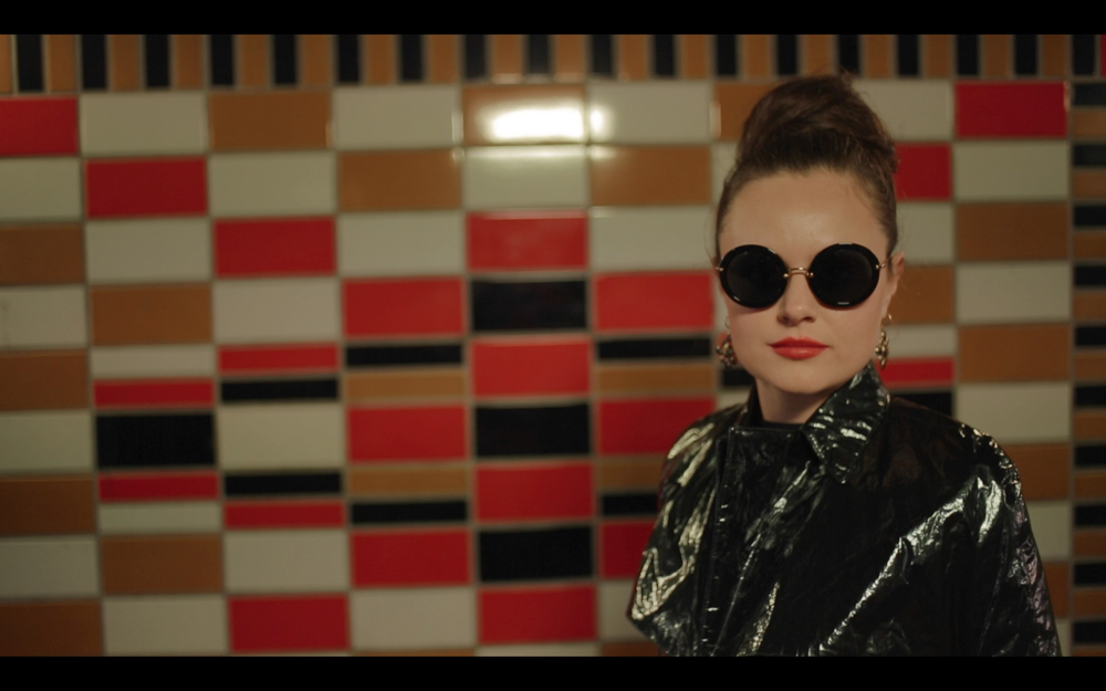"""Sophia Carr-Gomm as lead """"Georgie"""" in the Elephant&Castle underpass, wearing a trench from Fyodor Golan AW14."""