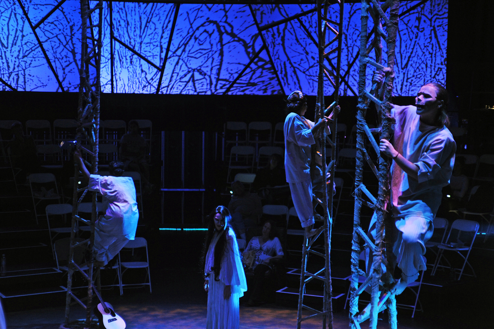 Scenic design by Jake Pinholster; Costume design by Connie Furr; Mask design by Zarco Guerrero; Lighting design by Celeste Brown; Media design by Daniel Fine with Matthew Ragan. Photo credit: Tim Trumble.