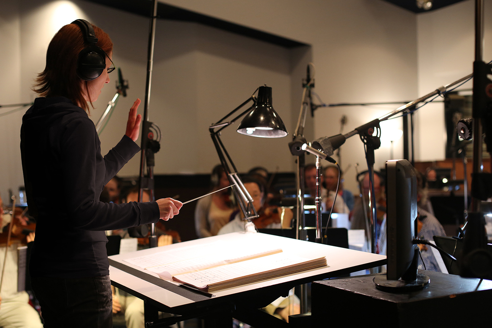 Katya Soudek composer conducting an 50-piece orchestra at Studio X in Seattle with Reed Ruddy
