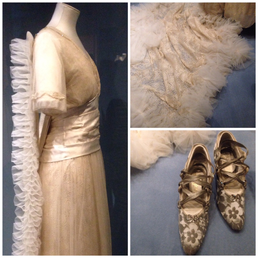 This gown, by Aida Woolf, is from 1914 and features a detachable train that would allow the wedding dress to be converted into a gown suitable for the newlywed bride to be presented at Court after her wedding. The silk brocade shoes are also beautiful and the outfit reflects the influence of evening dress fashions on the bridalwear of the time.