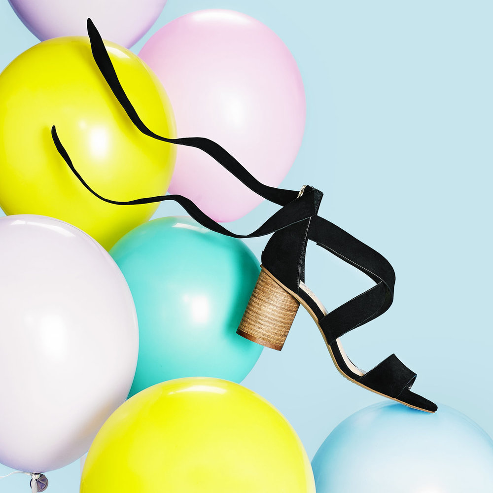 Black heel magically floating on pastel colored balloons.