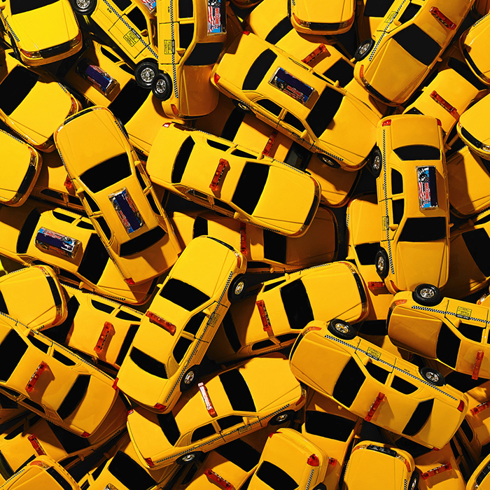 Still life of many miniature yellow taxis.