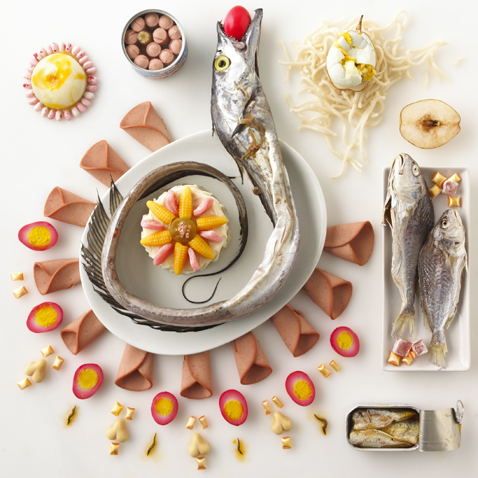Rotten food still life of fish holding pink egg in mouth
