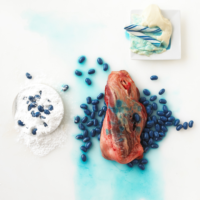 Rotten food still life of meat with blue jelly beans.