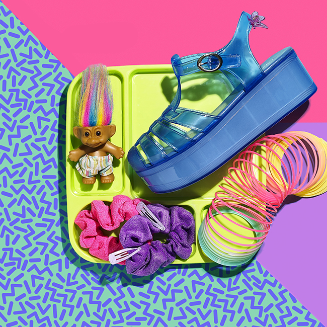 Conceptual still life photograph of 90s fashion featuring neon sandals, butterfly clips, and a troll doll.