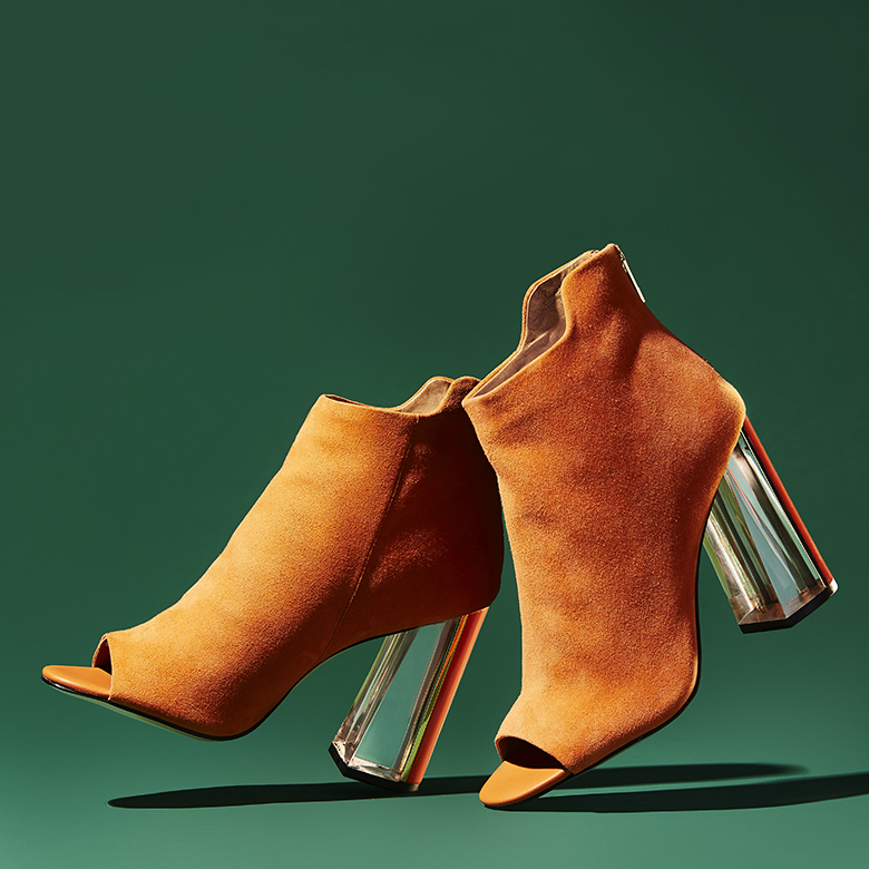 Photograph for Amazon Fashion's Social Media. Styling by Anna Lemi.  Orange wedge heels with transparent heels magically standing on green background. Photographed for Amazon Fashion.