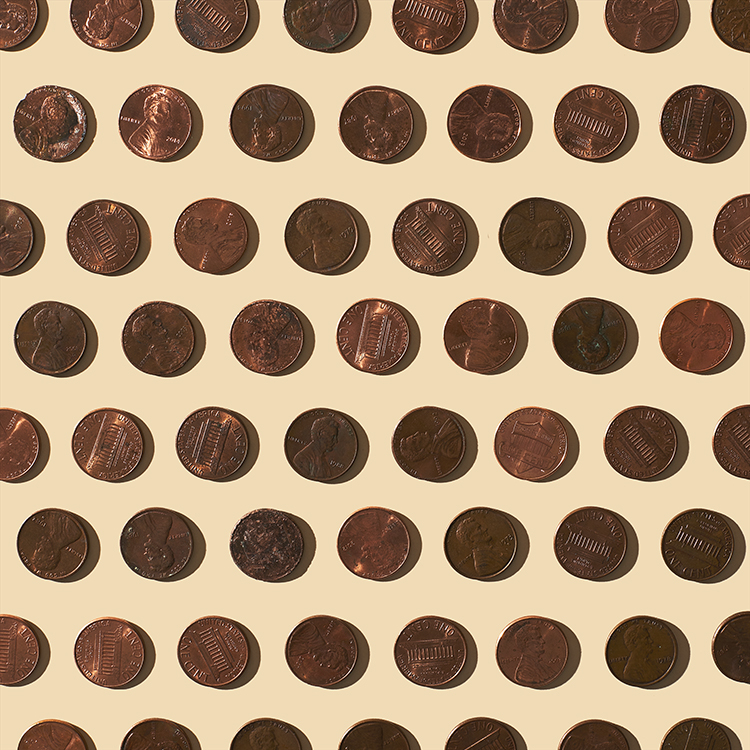 Conceptual Still life image of multiple pennies organized neatly on a beige background.