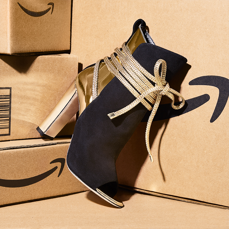 Photograph for Amazon Fashion. Styling by Anna Lemi. Conceptual still life image of a black velvet shoe resting on Amazon delivery boxes.