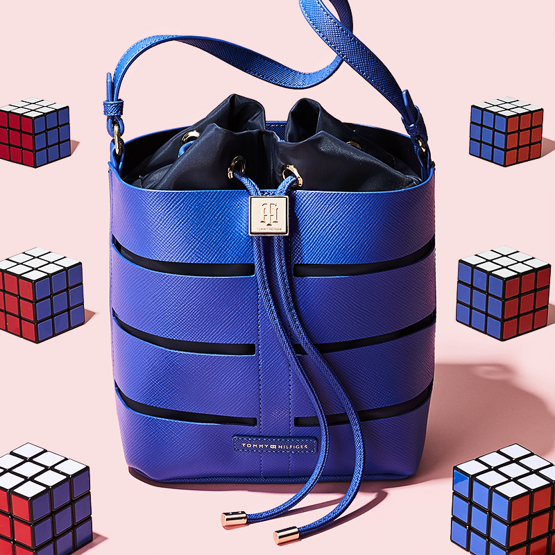 Styling by Anna Lemi.    Conceptual still life image of blue Tommy Hillfiger bag on a pink background with lots of rubix cubes.