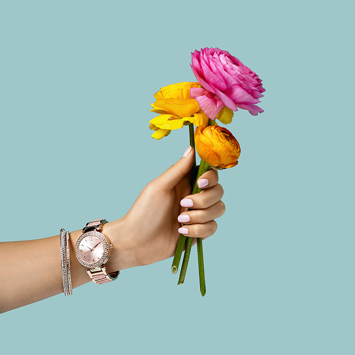Shot for Macy's. Styling by Rebecca Crea.   Conceptual still life photograph of a woman's hand holding flowers on a teal background.