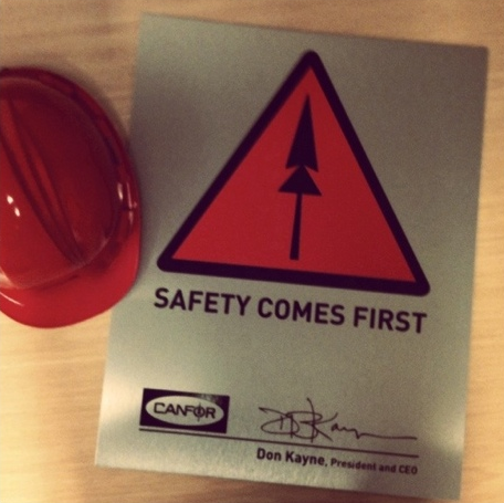 "The Canfor ""Safety Comes First"" sign and logo. The sign is highly visible in every Canfor operation and seen daily by over 6,000 employees."