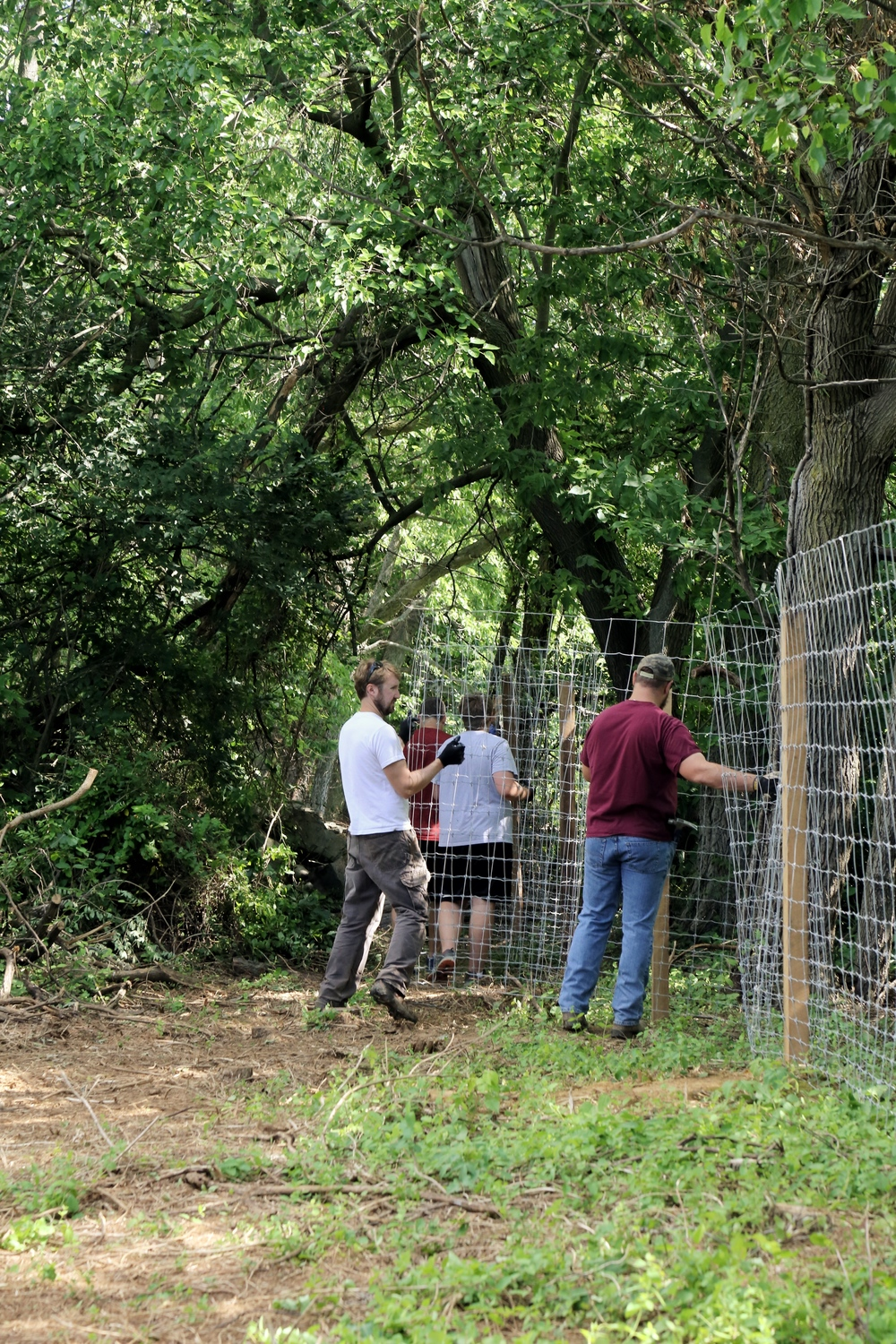 The fencing crew working on the back rocky stretch of fence. This one went through a rocky hill, between trees, and down a hill. Took us all day but it was worth it to see it done.