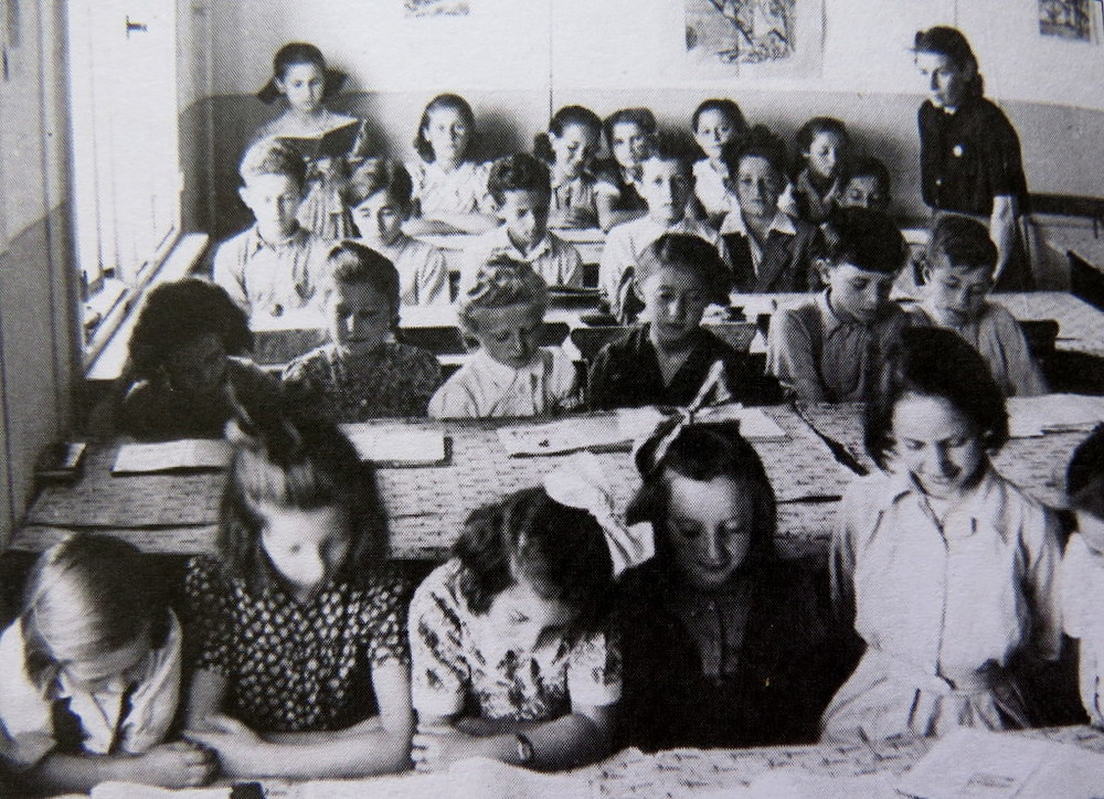 Judy standing, reading aloud to the class, back left corner, Schlachtensee DP camp, 1947