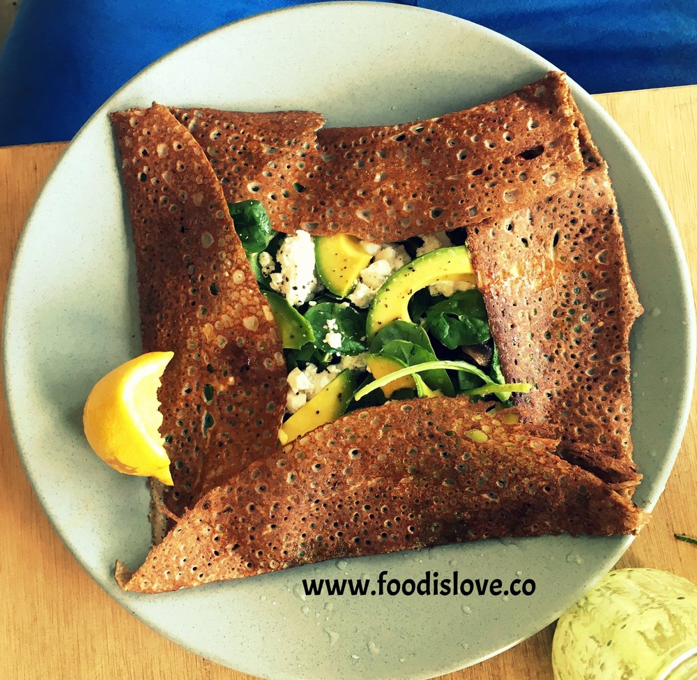 Gluten free buckwheat pancake filled with avocado, greens, feta and field mushrooms